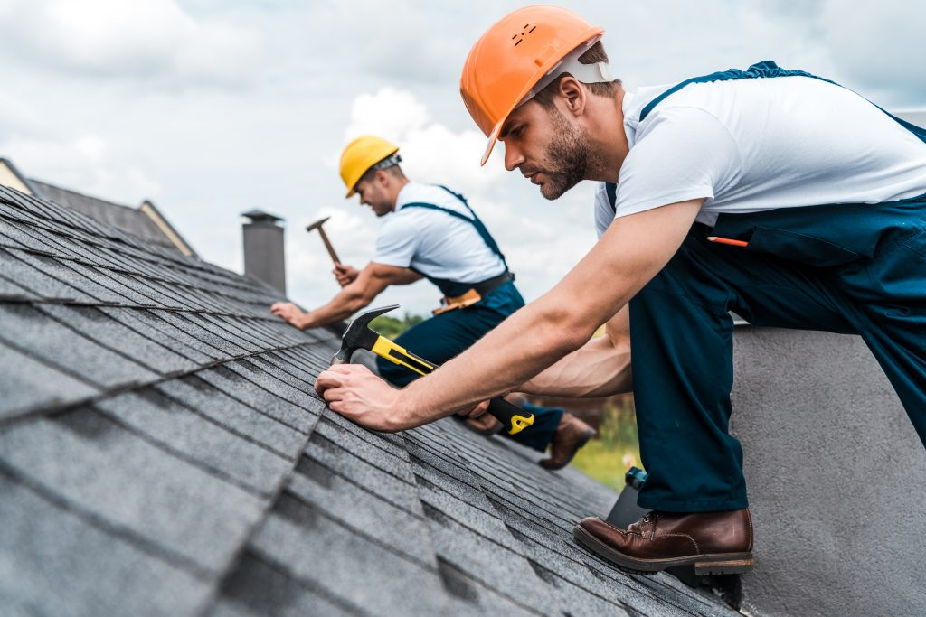two roofing experts fixing roof