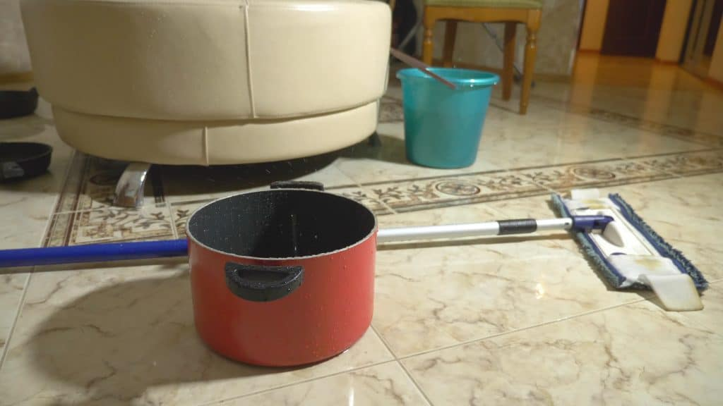 pots and pans collecting water from leaking roof