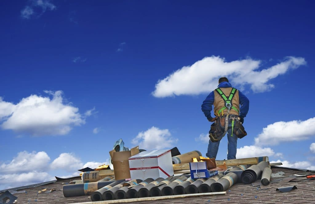 Roofer with materials on roof